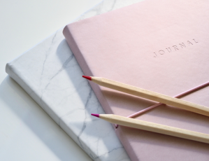 Photo of pink journal with two pencils on top.