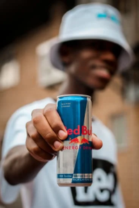 Image of man in hat (blurred face) holding can of red bull energy drink in front of him.